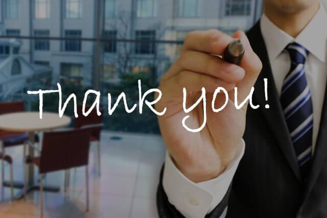 「Thank you」という文字を書くサラリーマンの男性