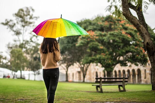 カラフルな傘をさす女性の後姿