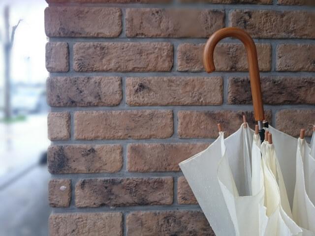 レンガの壁に立てかけられた白い傘