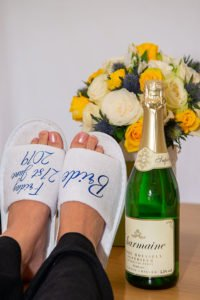 The coolest Bride ever in her Brides slippers with a bottle of bubbles and ber bouquet