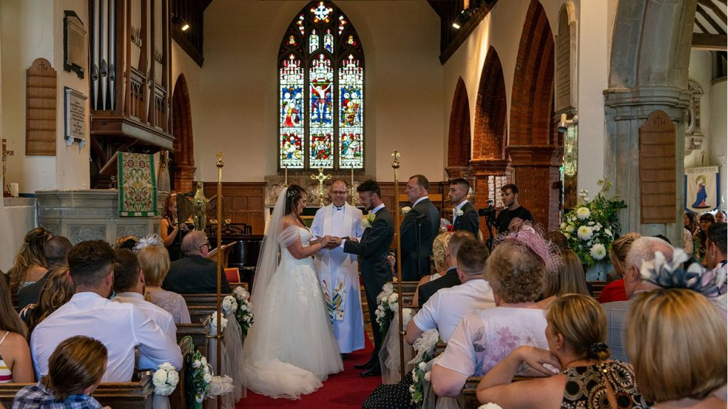 With this ring I thy wed, the view down the isle of the church to the couple standing with the reverend, exchanging wedding bands. Family sit in pews to the left and right.