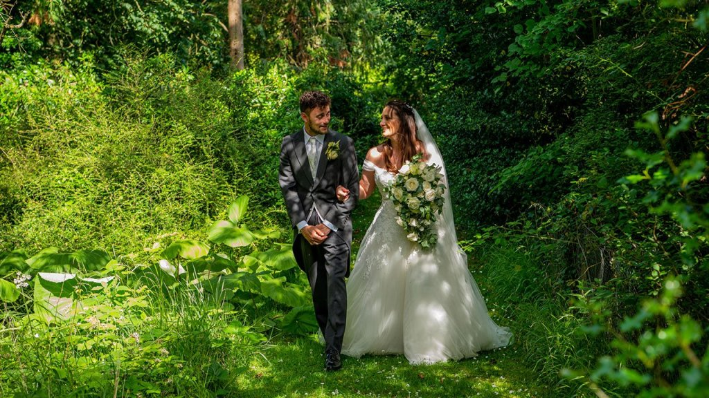 The Bride and Groom strolling in the cool woodland at Ingatestone Hall, with the mottled afternoon sun streaming through the trees