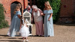 When the doves are moved into the centre of the court-yard at Ingatestone Hall before the release two family members, two adult bridesmaids and the little flower girl take a closer look.