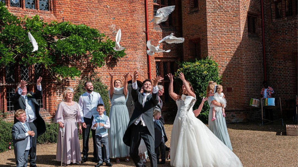 The wedding party are handed a dove each to release, the white doves fly into the air and sore above the wedding party