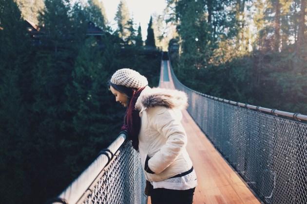 橋から下を見下ろす女性