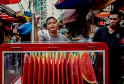 Mellon collie. A man sells freshly cut slices of watermelon along a busy alley in Manila. The Philippine population has reached over 100 million. 10% of which work overseas, mostly women. A quarter still live below the poverty line. January 2016