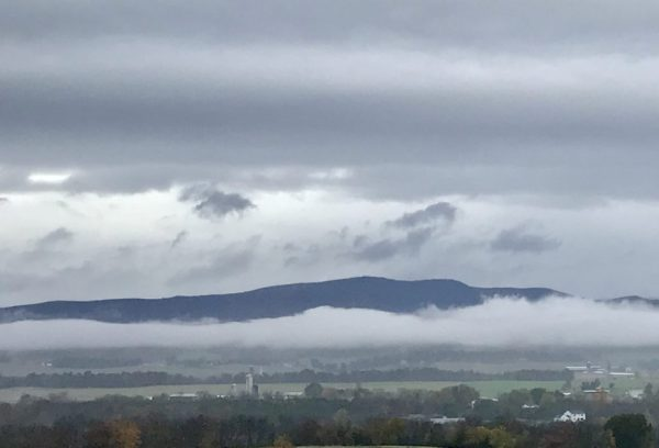 The Allegheny Mountains peek out from a layer of clouds above and below.