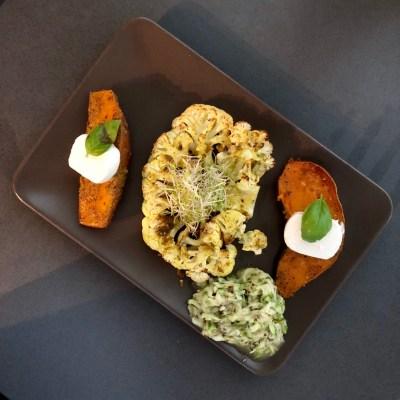 Gepofte zoete aardappel met gegrilde bloemkoolsteak en courgette vinaigrette salade