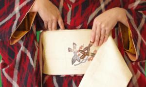 帯枕のヒモを帯の中へ入れる