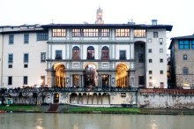 The facade of the Uffizi Gallery across the Arno River. The second floor shows the Vasari Corridor that links the Uffizi Gallery to the Palazzo Pitti. Once used by the Medici family, it is now a private gallery hung with self-portraits of many of the masters. Reservations are needed in order to visit.