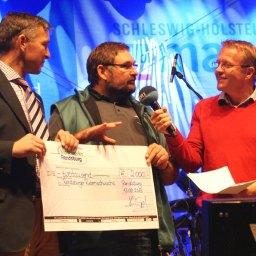 Achim Czesnat, Vorsitzender des Rendsburger Rudervereins e.V., erhält einen Scheck zur Nachwuchsförderung