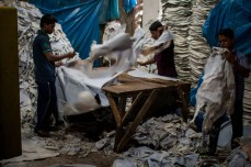 Workers cutting and fixing dried hide in a tannery.