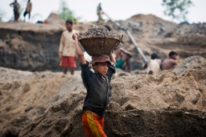 An under-aged labour carrying heavy load of stones on his head.