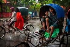 Rickshaw pullers taking a break in their rickshaw during the rain.