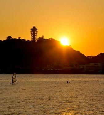 片瀬東浜から金色の夕日に輝く江ノ島とパドルサーフィン