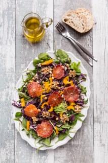Salatplatte mit gemischten Salat, Quinoa tricolore, Kichererbsen, gelber Paprika, Walnüssen, Rotkohl und Blutorangen, Baguette, Karaffe mit Dressing, Studio