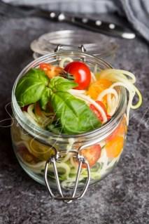 zoodels im Glas mit Tomaten und Basilikum, Gabel,