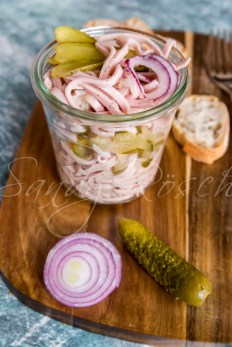 Wurstsalat mit roter Zwiebel und Essiggurke im Glas, auf einem Holzbrett stehend, Baguettescheiben, blaugrauer Untergrund