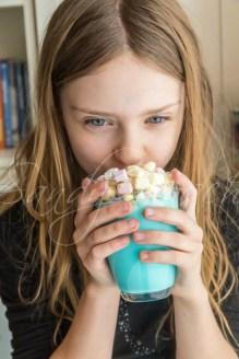 Mädchen trinkt blaue Milch mit Marshmallows und bunten Zucherkonfetti, Unicorn milk, Studio