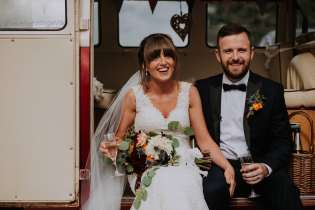 Bride and groom with wedding camper van