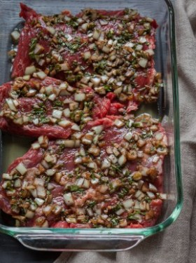 Raw skirt steak marinating in raw chopped onions and herbs in a glass dish.