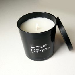 Open burning black candle with Erase the Darkness handlettered on it.