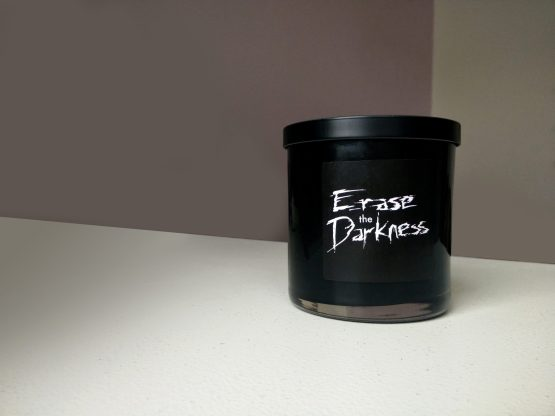 Black Erase the Darkness candle on white table.