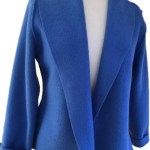 A sapphire blue fitted wool jacket featuring a back peplum and shawl collar handmade by Sandra Hardy