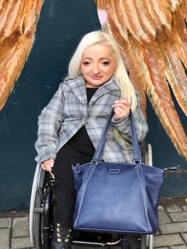 Sam Renke holding her accessible wheelchair handbag in navy