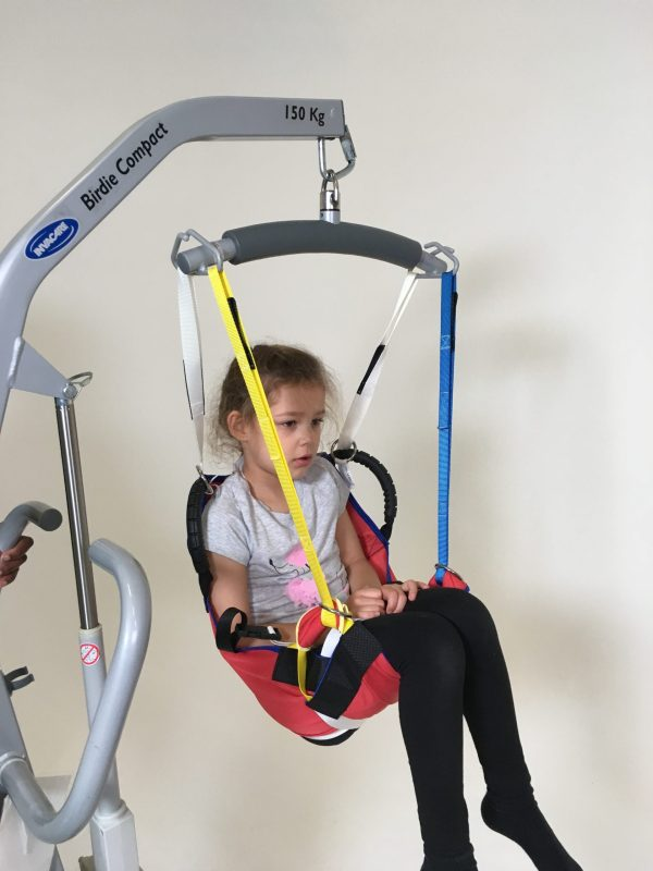 Disabled girl being moved in ProMove sling with straps attached to the hoist