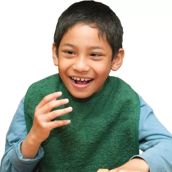 Disabled boy wearing Seenin bib apron in green