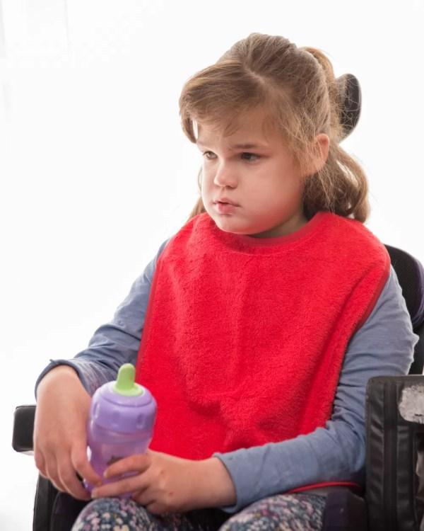 Disabled girl wearing Seenin bib apron in red