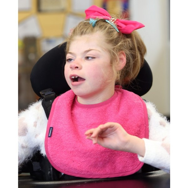 Disabled girl wearing Seenin bib in pink