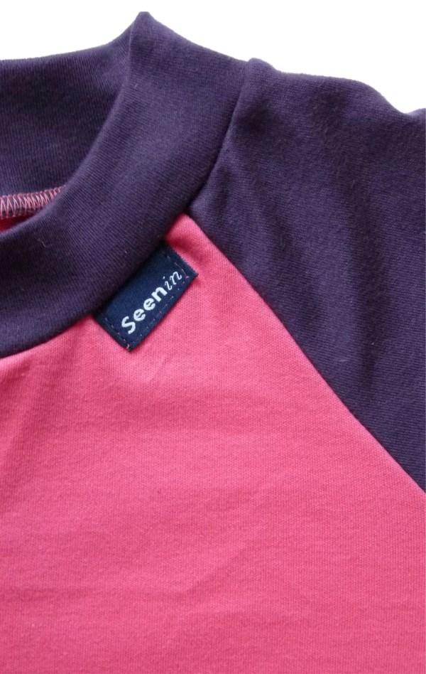 Close up of front of Seenin children's pink and plum zip sleepsuit