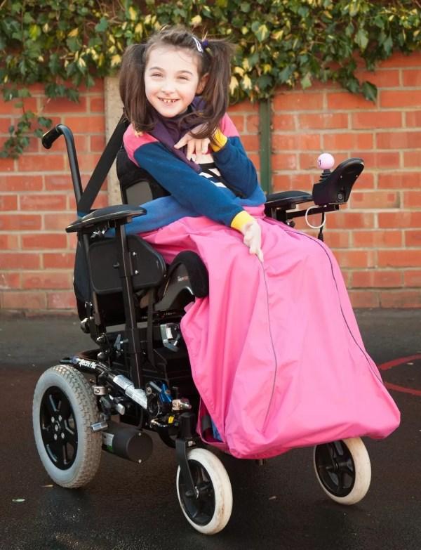 Disabled girl wearing pink Seenin waterproof wheelchair leg cover