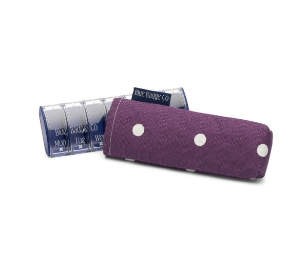 Image is a photograph of a plastic pill box with a dark purple with white spot-designed case cover.