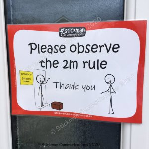 "Image is a photograph of a poster attached to a door. On the poster a stickman waves and smiles from his front door, with a package at his feet, whilst another stickman smiles and is seen to be keeping 2 meters in distance away. Text reads: ""Please observe the 2m rule - thank you"""