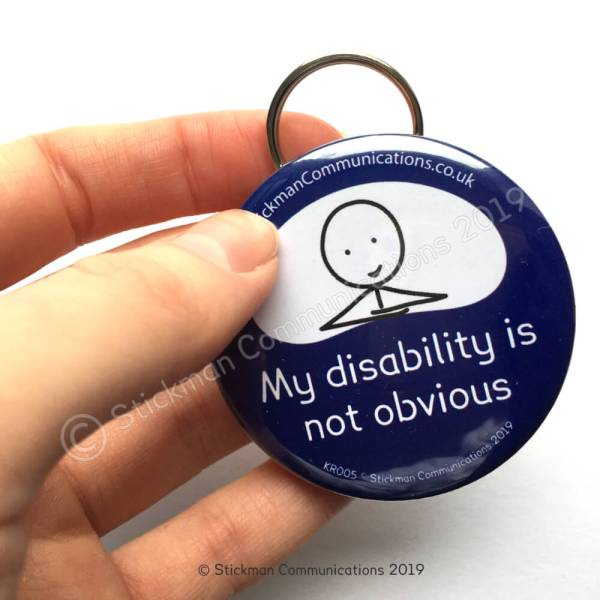 "Image is a photograph of a hand holding a blue, round keyring with a smiling stickman illustration, with text which reads: ""My disability is not obvious"""