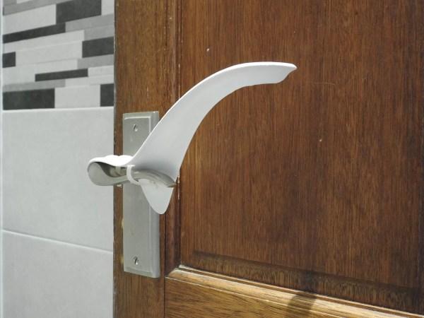 Image shows an internal wooden house door with the plastic Tru Grip door handle extender installed