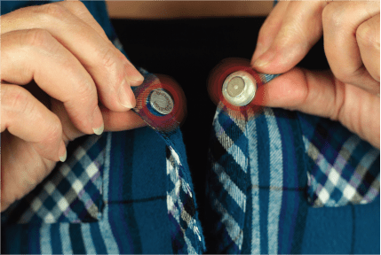 Image is a photograph of the close-up of the neck of a man wearing a blue, checked shirt fitted with magnetic buttons