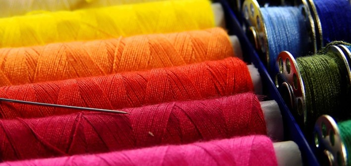 Row of reels of threads in rainbow colours