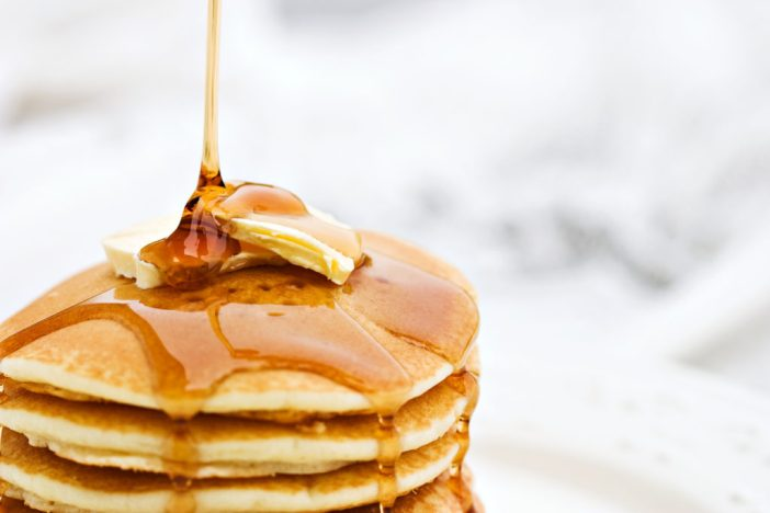 Maple syrup pouring onto pancakes.