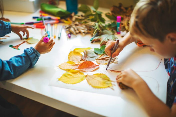 Kids making crafts with fall leaves