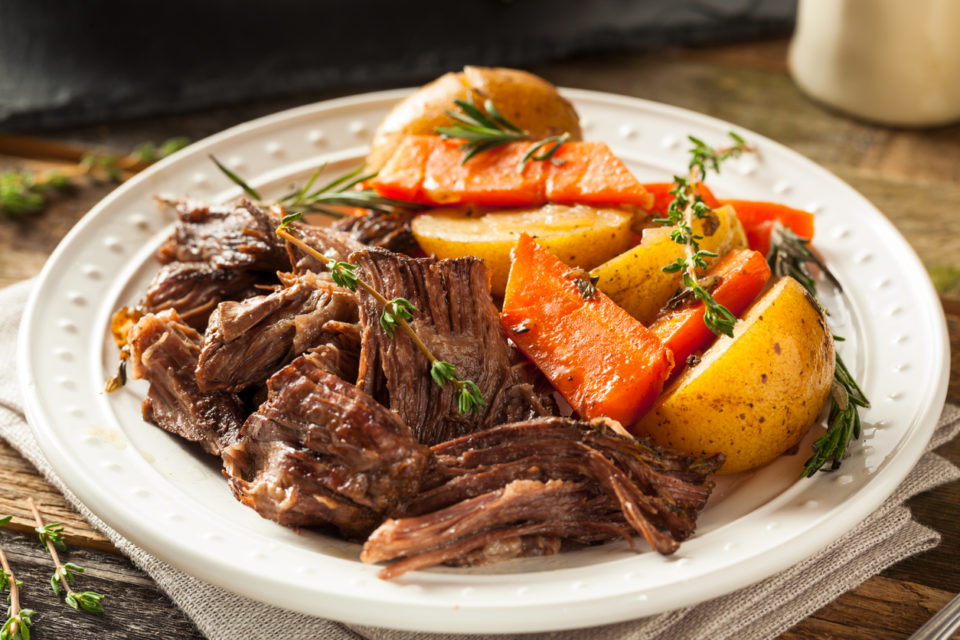 Pot roast, carrots, and potatoes on a white dinner plate