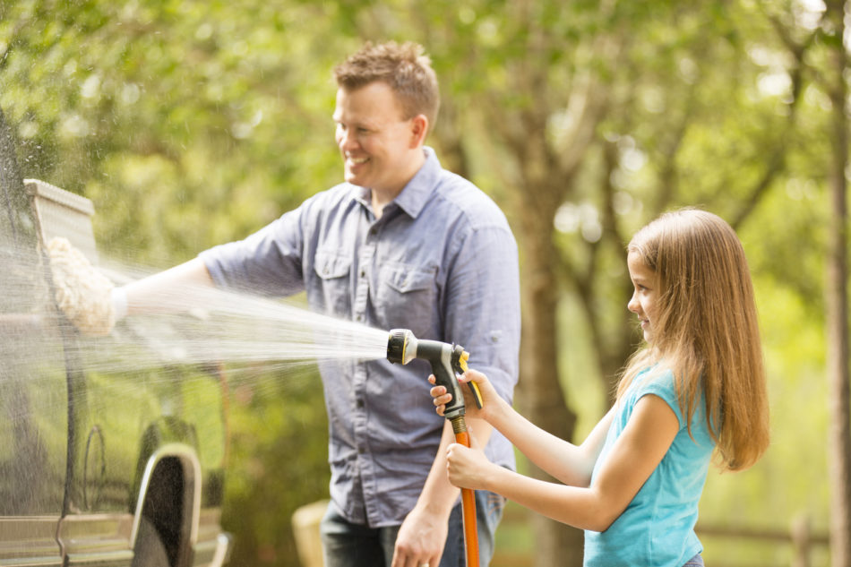 Father and daughter washing their car on the driveway