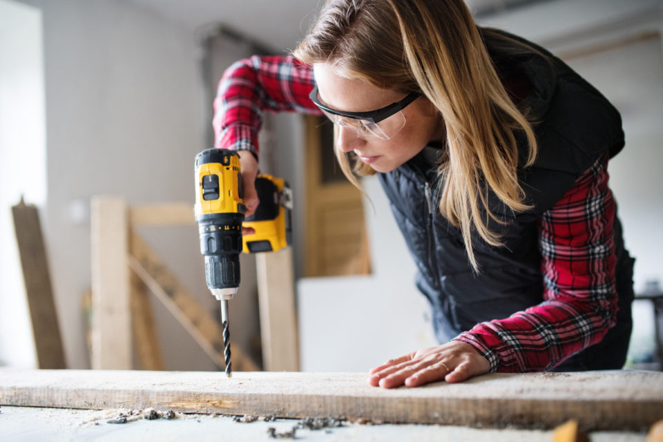 Young woman worker in workroom. Female carpenter using drill.