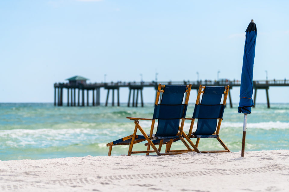 Okaloosa fishing pier in Fort Walton Beach, Florida in Panhandle, Gulf of Mexico on summer sunny day, two empty beach recliner lounge chairs umbrella