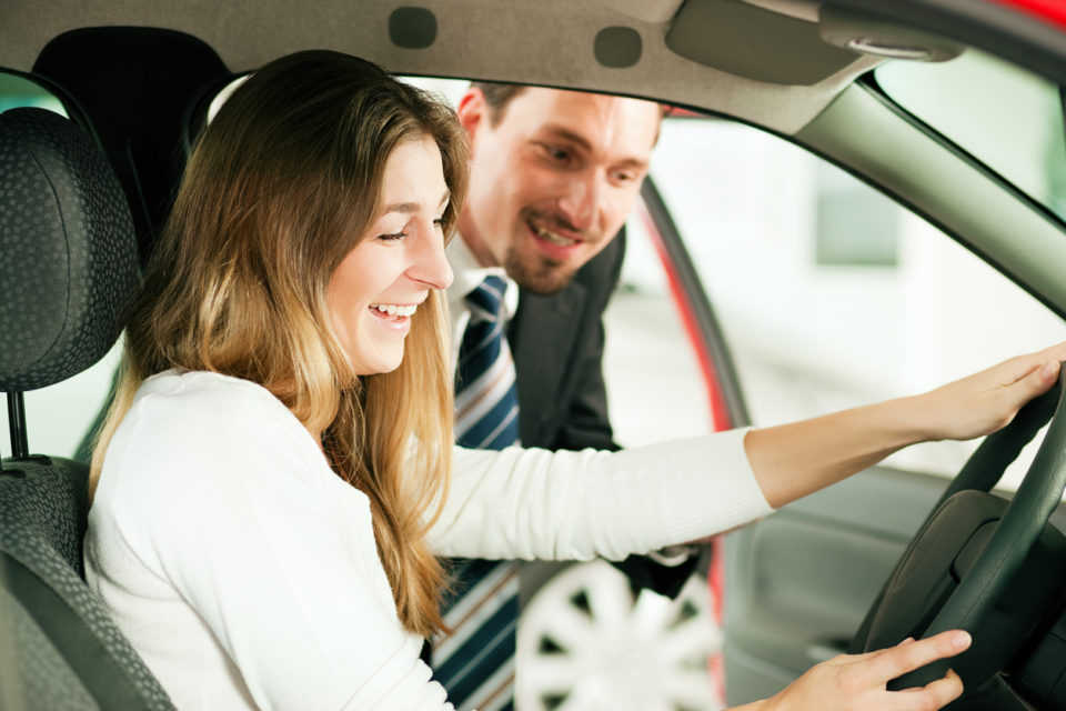 Car dealership customer sitting in a vehicle while a sales associate assists her