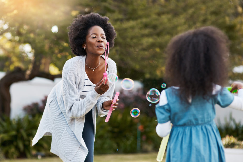 Shot of a mother and her daughter playing with bubbles together outdoors