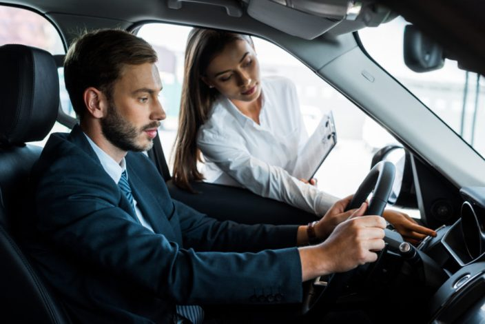 woman holding clipboard and pointing with finger at button near steering wheel